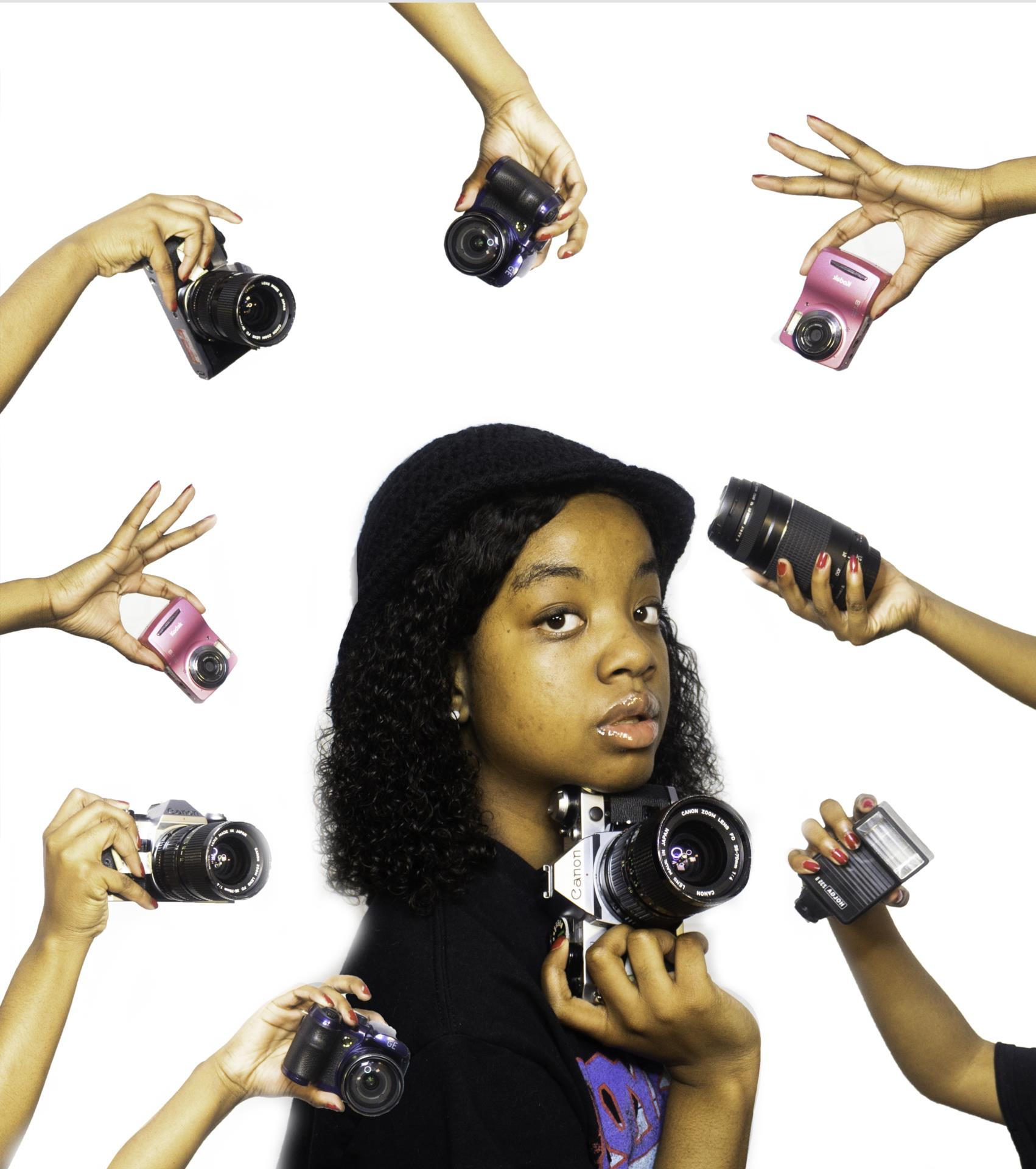 Senior Maya Peroune holding a camera with many hands holding cameras around her