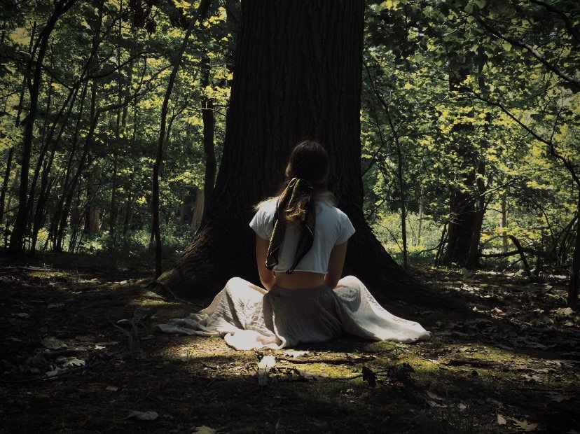 Girl in flowing skirt sitting with her back to the camera looking at a large tree trunk.