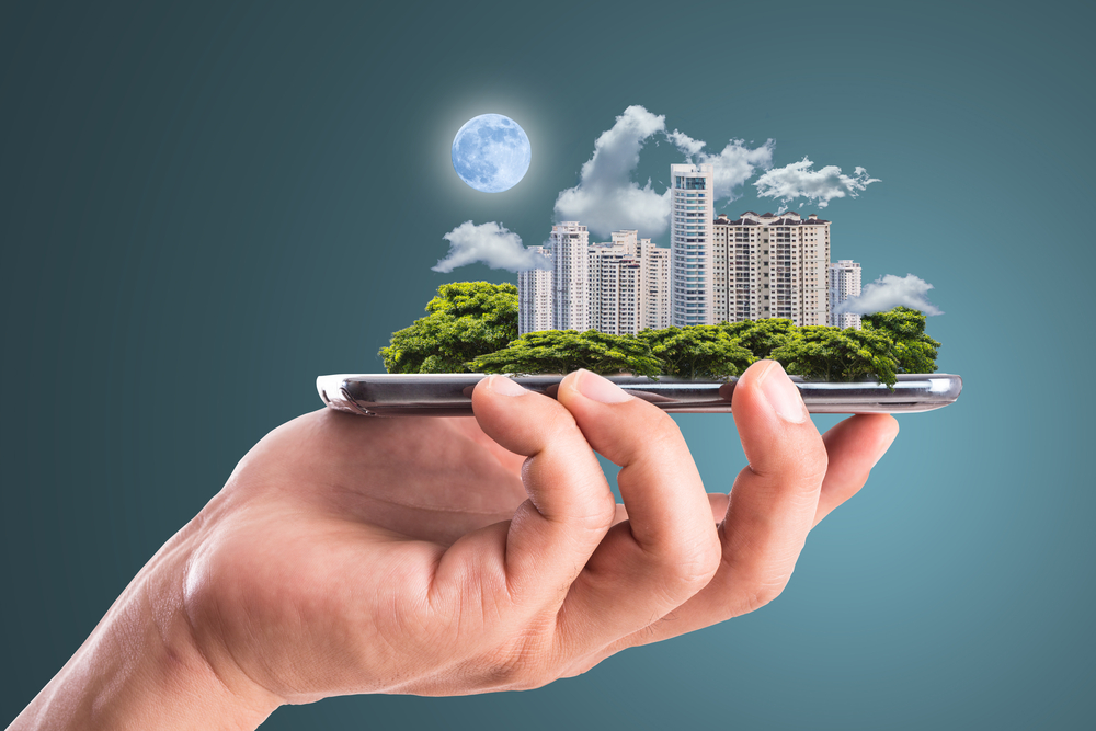 Hand holding digital city emerging from smartphone