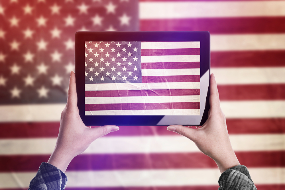 Person holding tablet in front of American flag