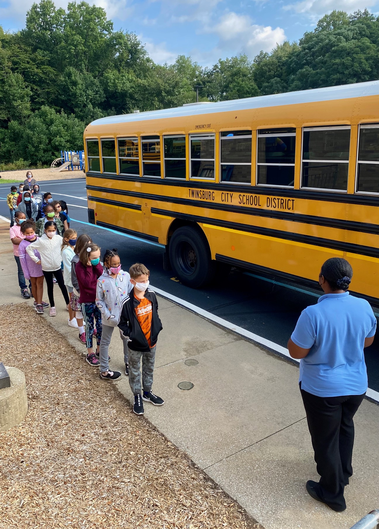 students standing outside of a school bus with bus driver learning bus safety