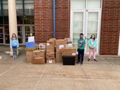 students standing around boxes of donated food