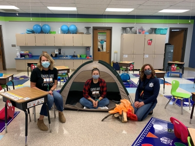 teachers in classroom; one in a tent