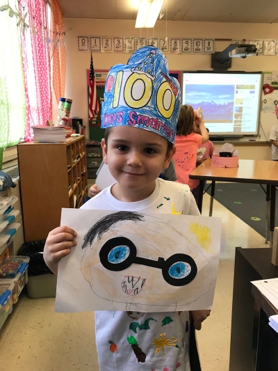 student wearing 100 day headband and holding artwork