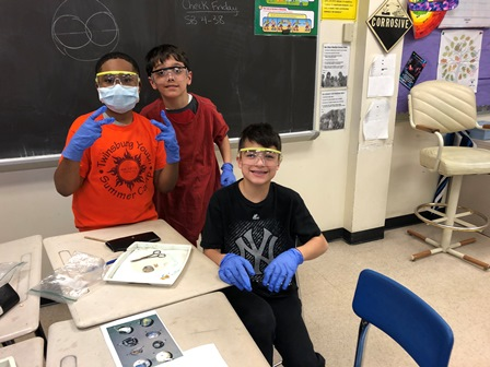 students wearing masks and gloves participating in a sheep eye dissection