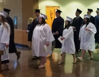 students dressed in caps and gowns walking into baccalaureate