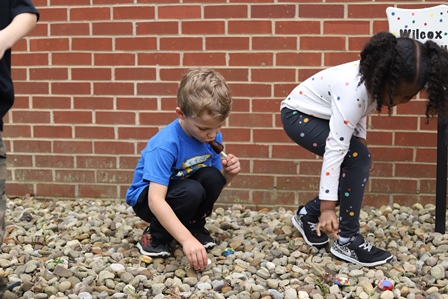 students putting painted rocks in a rock garden