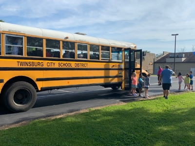 students and driver standing outside of a school bus
