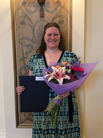 staff person holding flowers and certificate