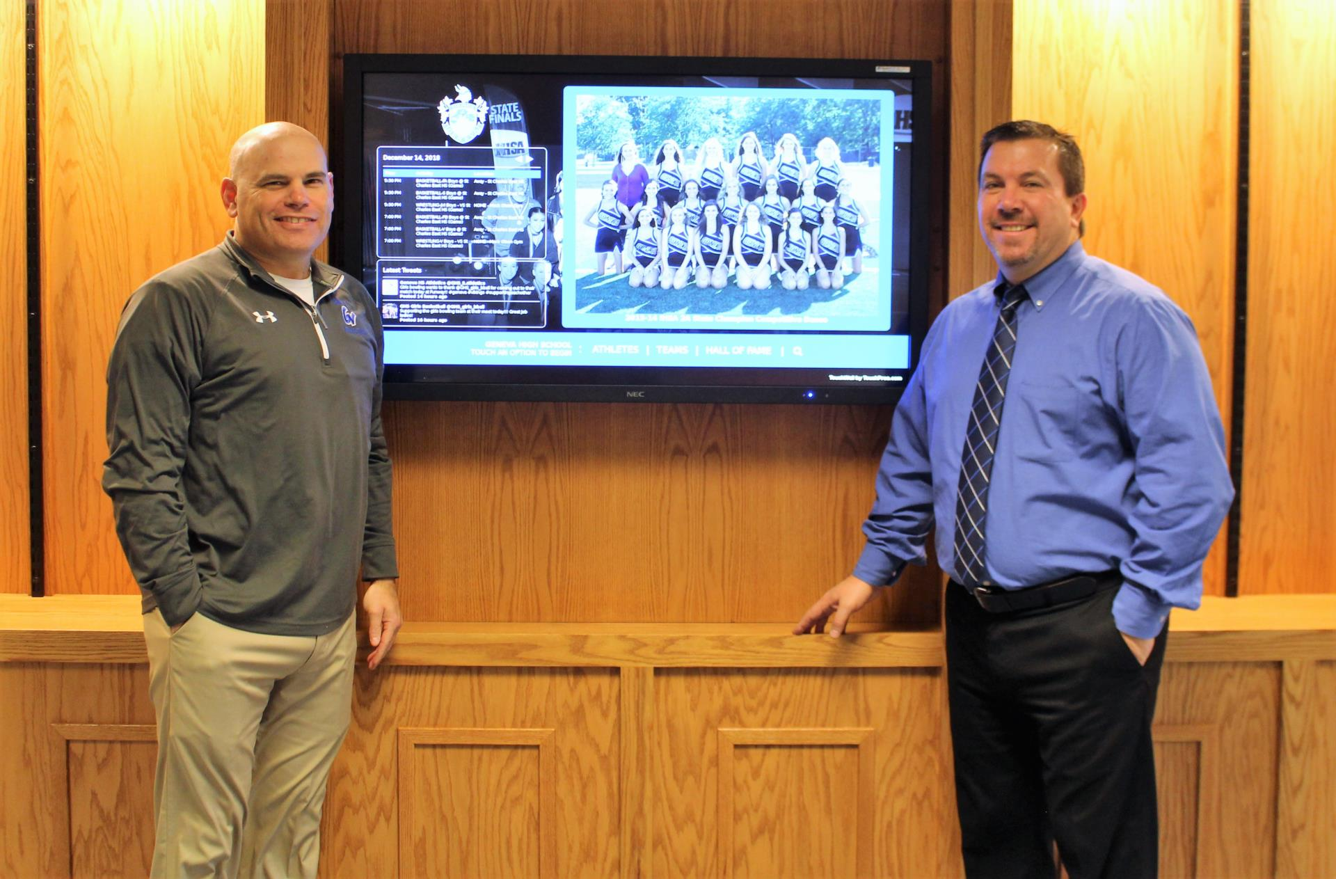 Athletic Director Dave Carli (right) and Assistant Athletic Director Matt Hahn unveil the interactive, touchscreen monitor in the GHS Contest Gym Foyer.